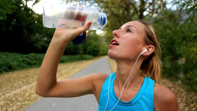 Beautiful and sporty young woman drinking water after jogging outdoors