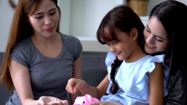 beautiful asia woman their savings Coin in a piggybank