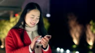 beautiful asian girl using smart phone in modern city at night