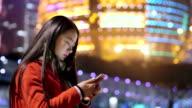 beautiful asian girl using smart phone in modern city at night