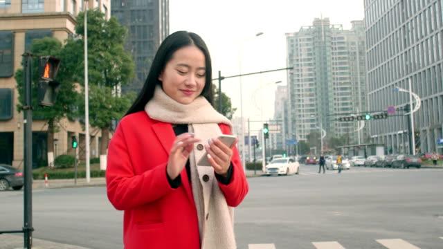 mooi Aziatisch meisje met behulp van slimme telefoon in de moderne stad