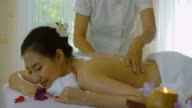Beautiful Asian woman Enjoying Massage therapy with essential oils
