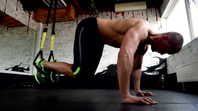 beautiful athlete is pushed on trx straps