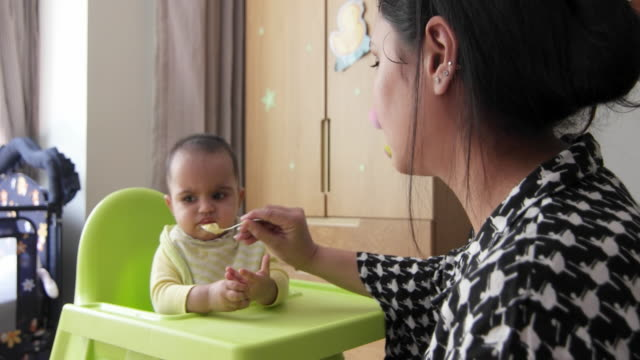 Beautiful baby refuses initially but finally gives in and eats food by her mom, seated on a high chair