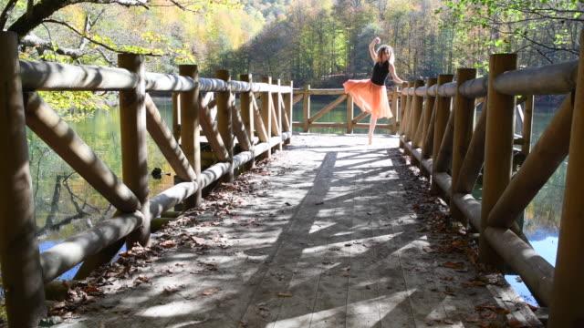 beautiful ballerina dancing on the wooden wharf near the lake in autumn season