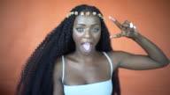 A beautiful black woman on an orange background.