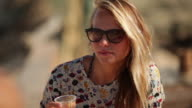 Beautiful blonde woman sitting at beach bar, drinking orange juice, talking to friend, smiling in the South of France.