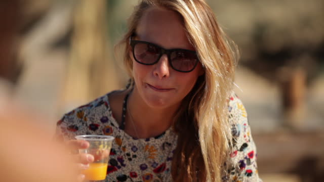 Beautiful blonde woman, smiling, drinking orange juice at a beach bar in the summer in the South of France.