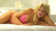 Beautiful blonde woman wearing pink lingerie in bed