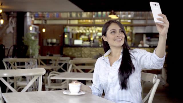 Mooie brunette genieten van een kopje koffie en het nemen van een selfie