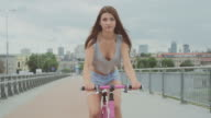 Beautiful brunette girl cycling in big city. Single speed city bike. Recorded with RED EPIC camera. 90 fps