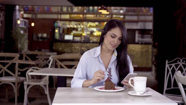 Mooie brunette sociale netwerken op haar smartphone terwijl u geniet van een taart