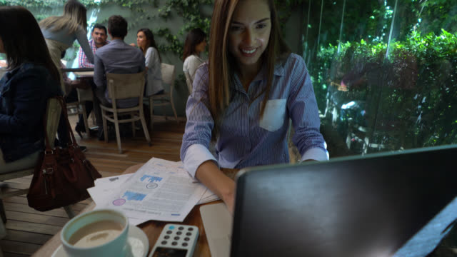 Schöne Brünette arbeiten auf ihrem Laptop und Notizen auf Dokumente suchen glücklich