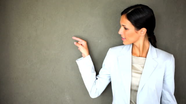Beautiful businesswoman pointing at copy space