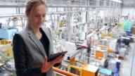 Bellissima donna d'affari lavorando su tavoletta fabbrica futuristico