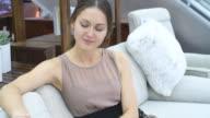 Schöne unbeschwerte Frau wählt sofa