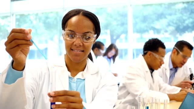 Schöne Chemie-Studenten oder Chemiker Tropfen Flüssigkeit in Reagenzglas