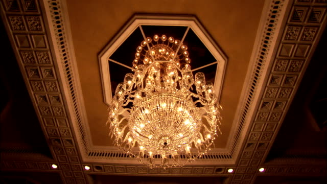 A beautiful crystal chandelier hangs from the ceiling of the Taj Mahal Hotel dining room Available in HD.