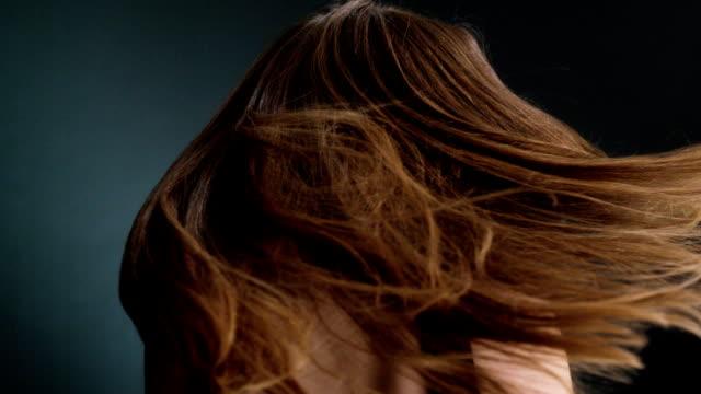 Beautiful dark blond woman flipping long hair