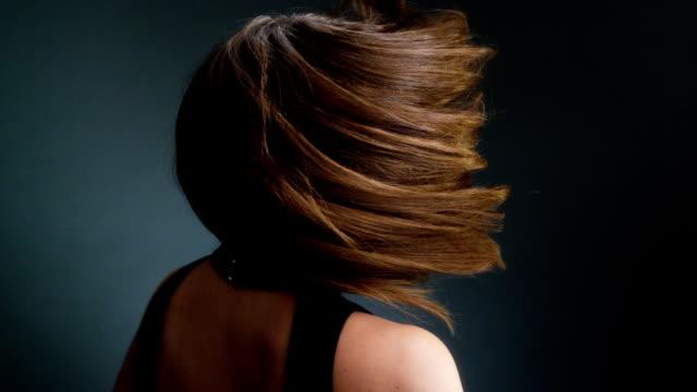 Mooie donker blonde vrouw gooien van lang haar