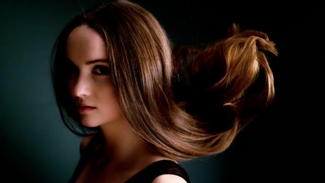 Schöne dunkel blonde Frau warf lange Haare