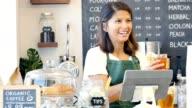 Beautiful female barista takes a female customer's order in a local coffee shop