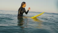 Beautiful female surfer sitting on surfboard in waves at Atlantic ocean coast in the south of France.