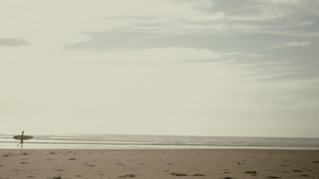 Beautiful female surfer walking alone on deserted beach, carrying surfboard