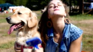 Beautiful girl brushing or grooming her golden retriever dog outdoors