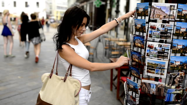 Beautiful girl choosing from postcard stand on the street.