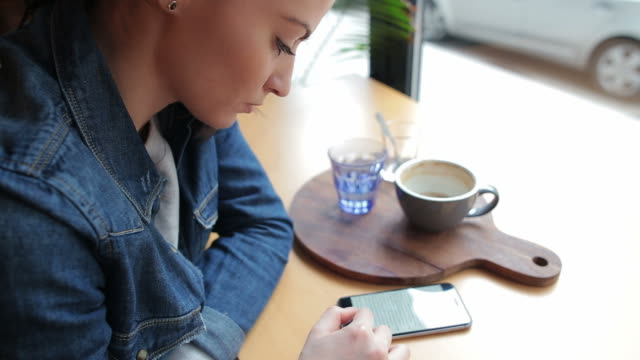 Beautiful girl in a coffee shop reading on her smart phone.