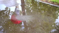 Beautiful girl jumps in a puddle on the road