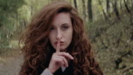 Beautiful girl showing silence sign in forest