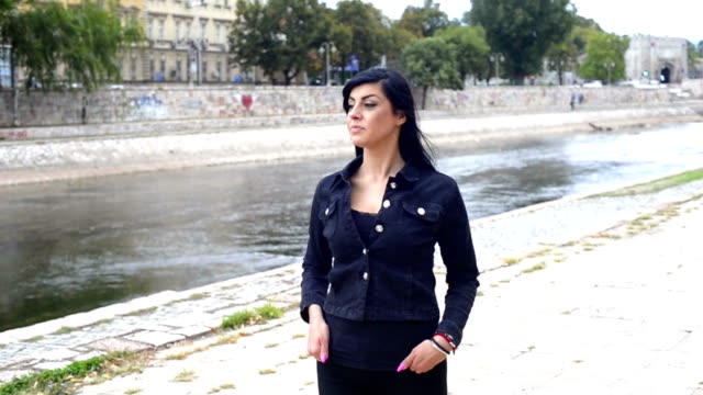 Beautiful girl walking by the river in the city