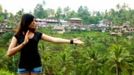Beautiful Indonesian young woman greets and shows terraced field HD
