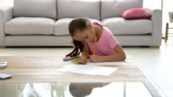 Beautiful little girl drawing at home