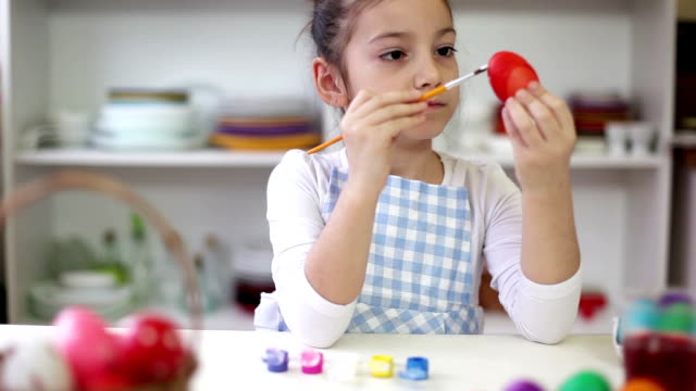 Beautiful Little girl painting Easter eggs