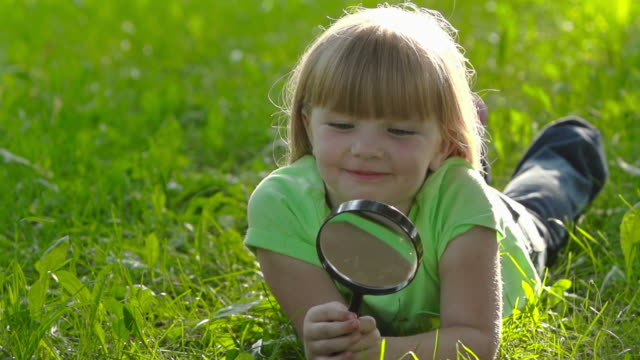 Beautiful little girl with magnifying glass