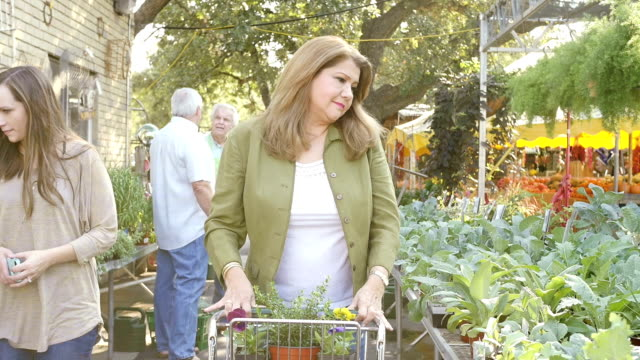 Beautiful mature Hispanic woman pushes shopping cart down aisle in plant nursery or farmer's market