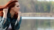 Beautiful red hair girl by the river enjoying the view
