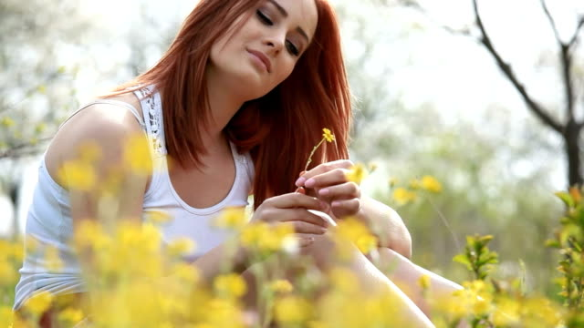 Beautiful red hair girl playing with flowers