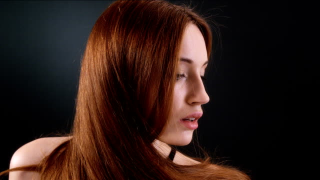 Beautiful redhead girl flipping her long hair