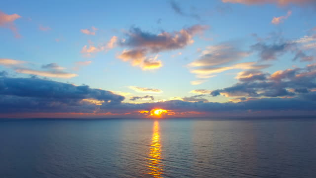 Beautiful reflections on water surface at sunrise,  aerial video