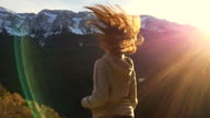 Beautiful russian girl move his long hair in slow motion with the beautiful snowy Pyrenees mountains during Christmas vacations travel in Catalonia.