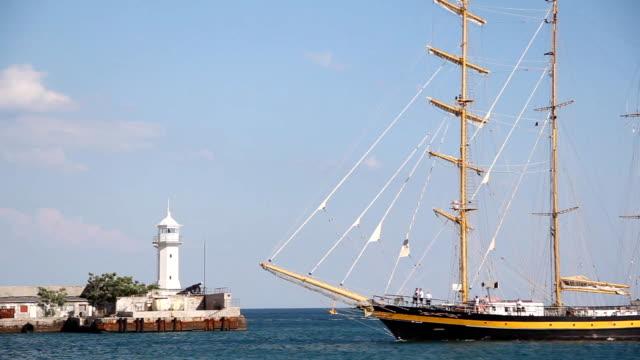 Wunderschöne Segeln Schiff auf dem Hintergrund der Jalta lighthouse