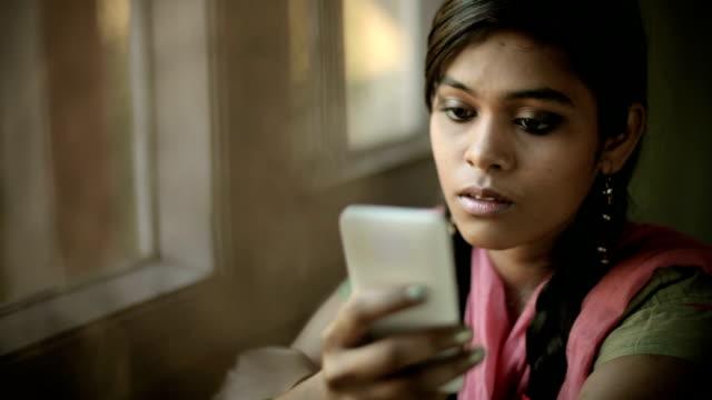 Beautiful serene Indian girl reading SMS sitting near window.