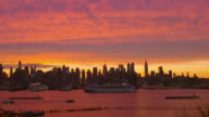 Beautiful shot of the Manhattan Skyline against a orange and blue sky during sunset, shot from across the Hudson River. Cruise Ships and other boats can be seen going along the Hudson River against a beautiful orange and blue sky
