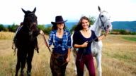Beautiful smiling women have a good time on a horse ranch