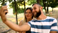 Beautiful stylish couple is using a smartphone and smiling while cycling in the park