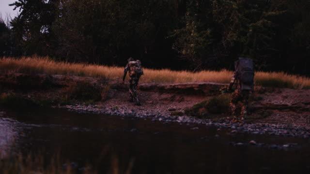 Einen schönen Sonnenuntergang Tänze abseits des Flusses als zwei Jäger schnell ein Tier nur nach Einbruch der Dunkelheit in Licht pirschen.